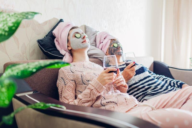 母亲和她的成人女儿应用了面膜和黄瓜在眼睛 变冷的妇女,当饮用酒时 免版税图库摄影