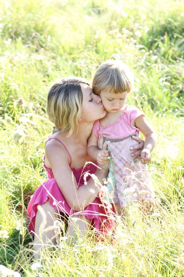 照顾和她的草的小女儿户外 免版税库存照片