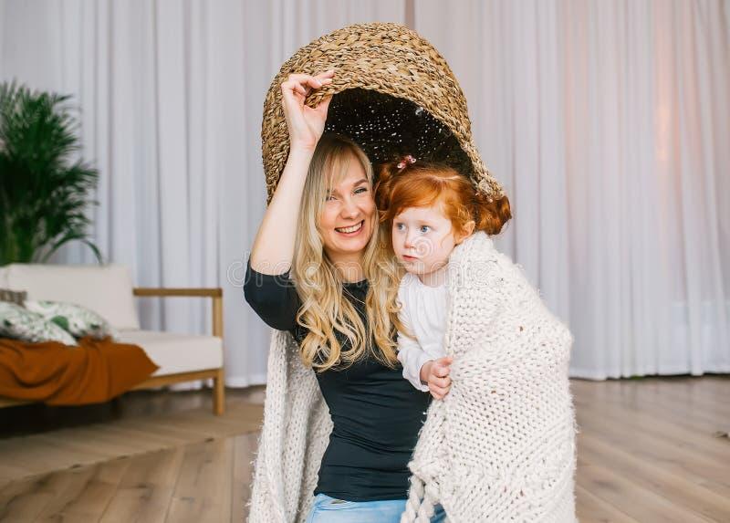 母亲和她的红头发人女儿在象帽子的头上把一个大篮子放 库存图片