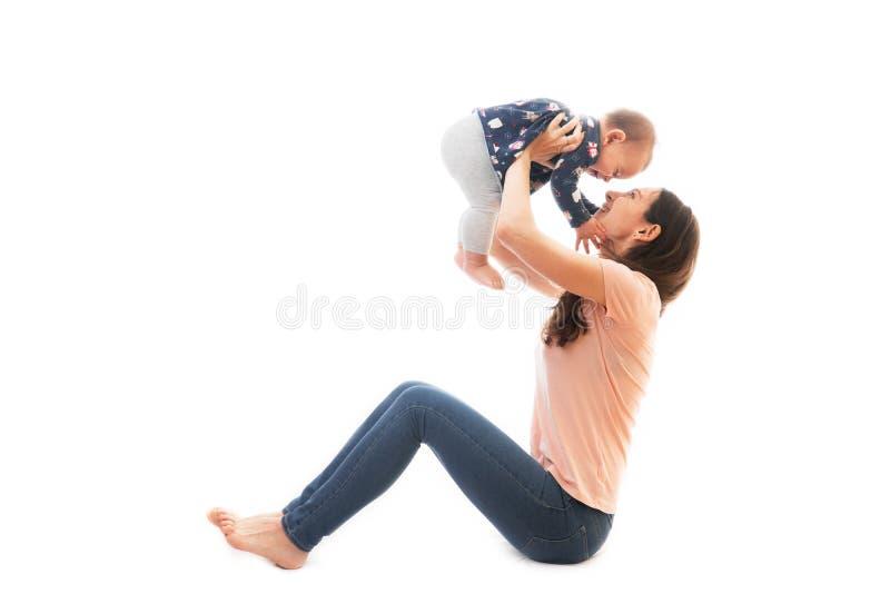 母亲和婴孩体操,在白色背景健身隔绝的瑜伽锻炼 免版税库存照片