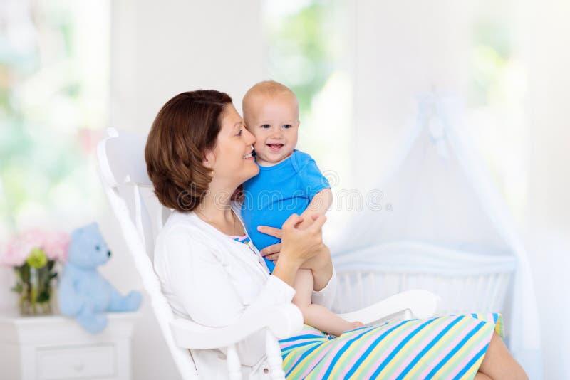 母亲和婴孩在白色卧室 免版税库存图片