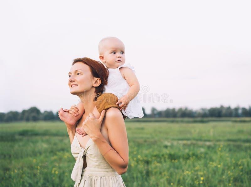 母亲和婴孩户外 在自然的家庭 免版税库存图片