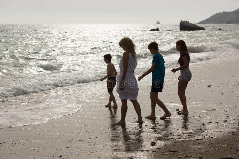 母亲和孩子享受他们的假期在沙滩和海水,在塞浦路斯的黄昏 图库摄影