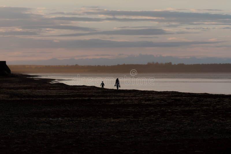 母亲和孩子作为剪影在日落探索和unkn 库存图片