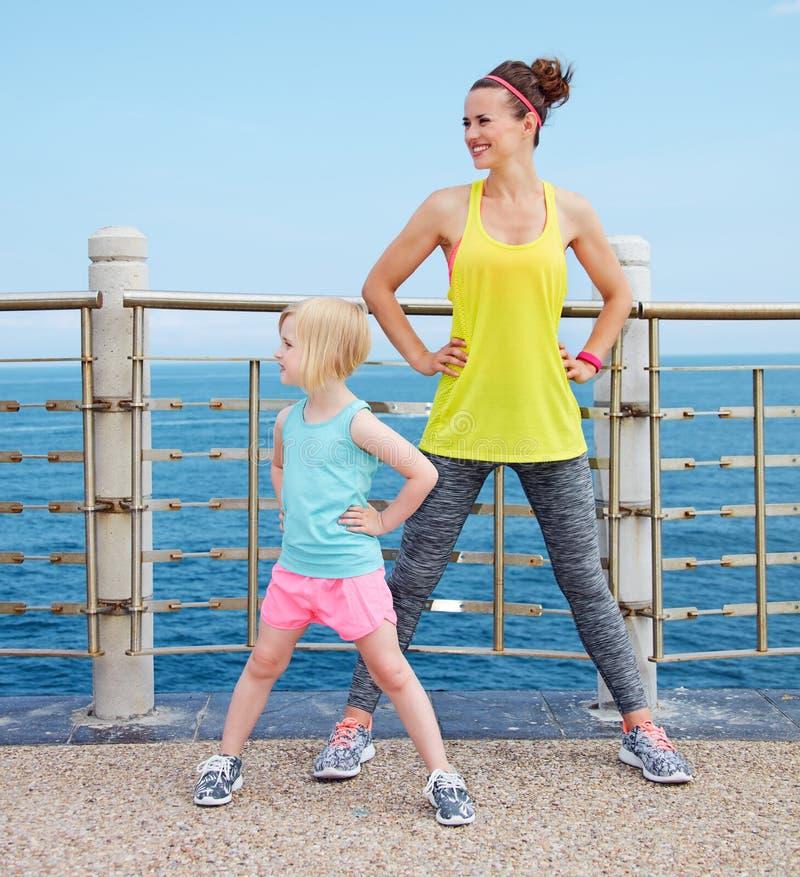 母亲和孩子健身的装备舒展在堤防 库存图片
