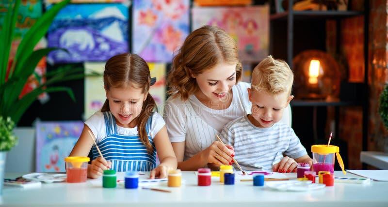 母亲和孩子儿子和女儿绘画在创造性画在幼儿园 库存照片