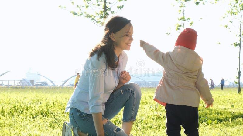 母亲和孩子嗅植物 走在公园的愉快的年轻家庭 免版税库存照片