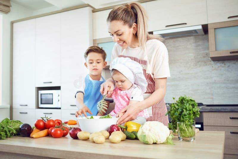 母亲和孩子在厨房里烹调 免版税库存图片