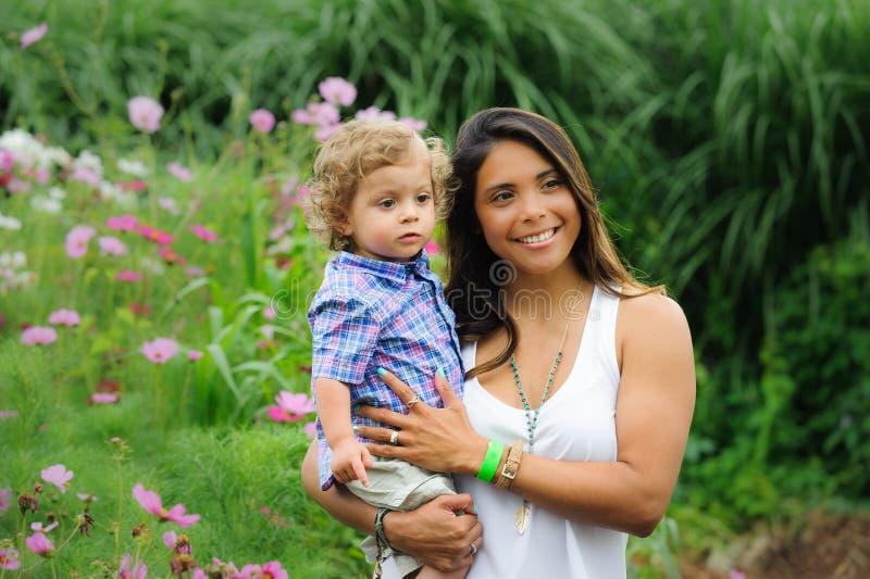 母亲和孩子在室外庭院里 免版税库存照片