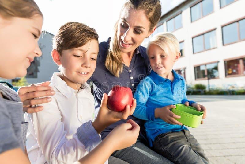 母亲和孩子在有的学校breaktime用苹果和lunchb 免版税库存图片