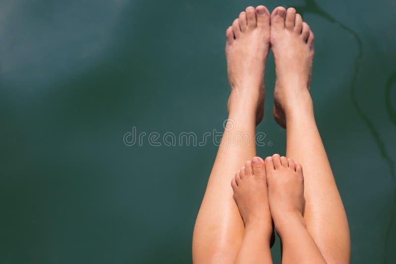 母亲和孩子在水中的浸洗他们的脚室外 免版税库存照片