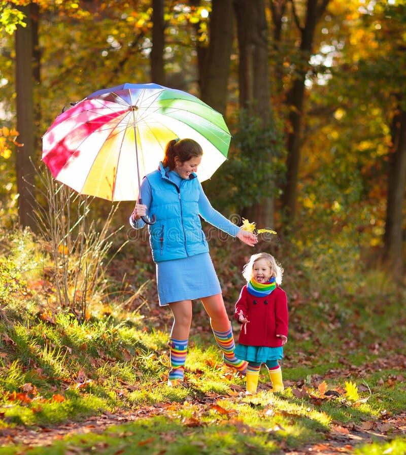 母亲和孩子在秋天公园 家庭在雨中 免版税库存图片
