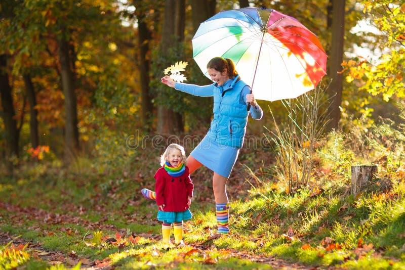 母亲和孩子在秋天公园 家庭在雨中 免版税库存照片