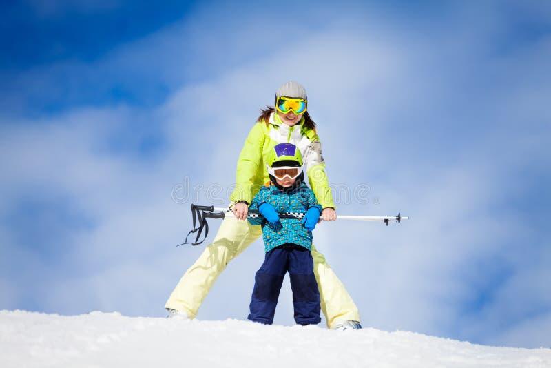 母亲和孩子在站立与滑雪的面具投票 免版税库存图片