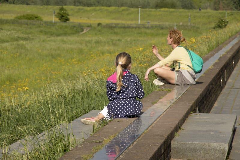 母亲和孩子坐堤防 图库摄影