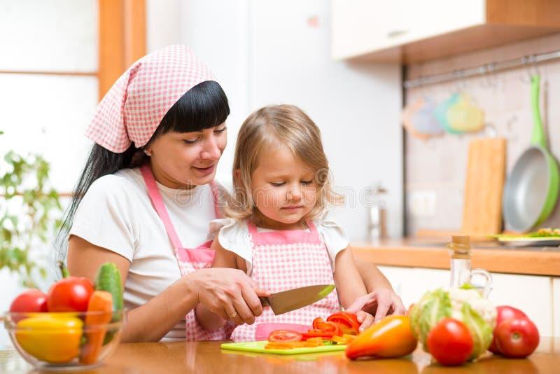 母亲和孩子女孩烹调并且切开了菜  库存图片
