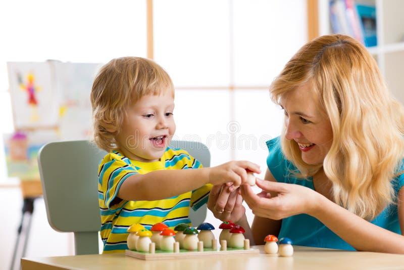 母亲和孩子学会颜色,估量,计数,当使用与发展玩具时 早期的教育概念 免版税库存照片