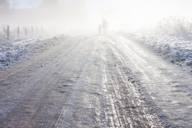 母亲和孩子有雾的雪农场马路的 图库摄影
