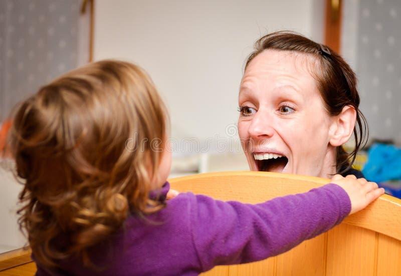 母亲和孩子演奏捉迷藏或捉迷藏 免版税库存图片
