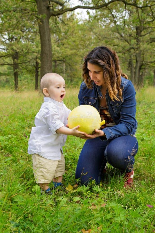 母亲和孩子用南瓜 免版税库存图片