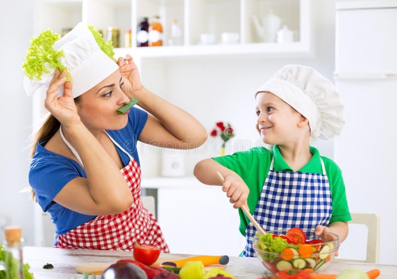 母亲和孩子获得乐趣在使用与菜a的厨房 库存照片