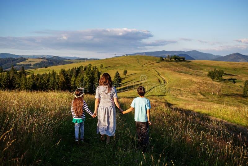 母亲和孩子获得乐趣在山 免版税库存照片
