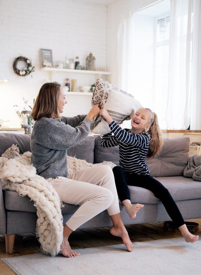 母亲和孩子获得乐趣在沙发床上的枕头战在卧室 一起花费时间的愉快的系列 免版税库存照片