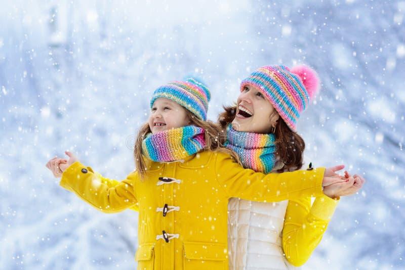 母亲和孩子被编织的冬天帽子的在雪 图库摄影