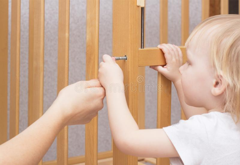 母亲和孩子装配一个小儿床,特写镜头,白种人,内部 免版税库存照片