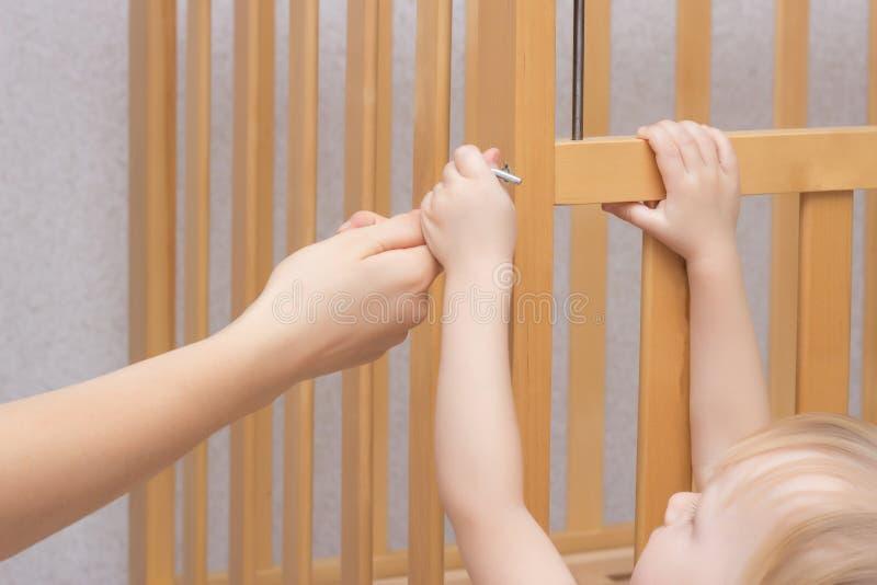 母亲和孩子装配一个小儿床,特写镜头,白种人,设施轻便小床 库存图片