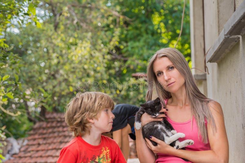 母亲和孩子,妈妈拿着一只猫 免版税库存照片