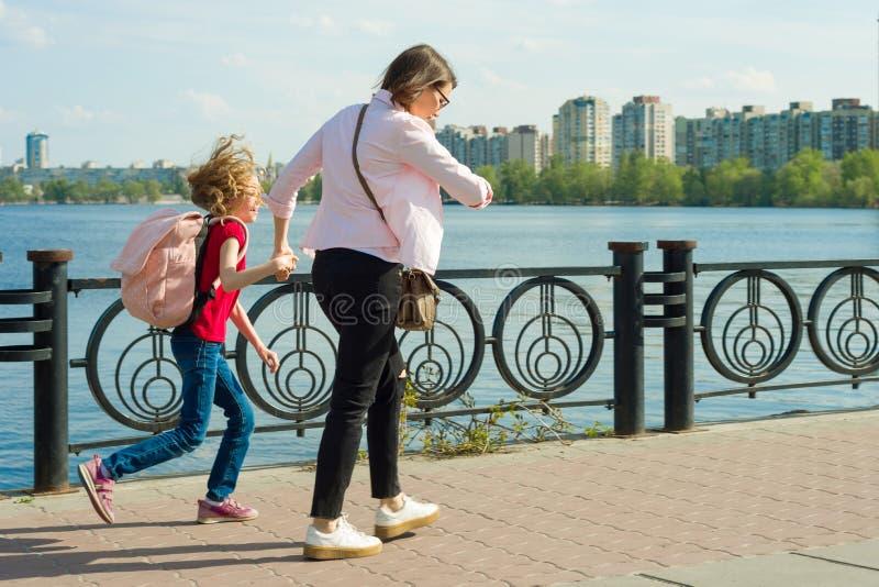 母亲和小女儿上学 妇女看她的手表,仓促,晚,迅速去 免版税图库摄影