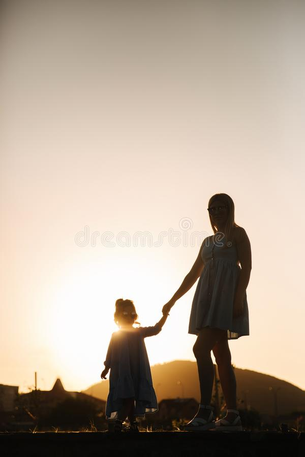 母亲和小女儿剪影  在杉木常设夏天日落结构树二之后 免版税库存图片