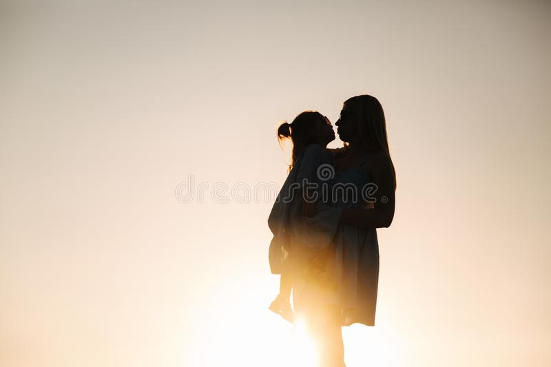母亲和小女儿剪影  在杉木常设夏天日落结构树二之后 库存图片