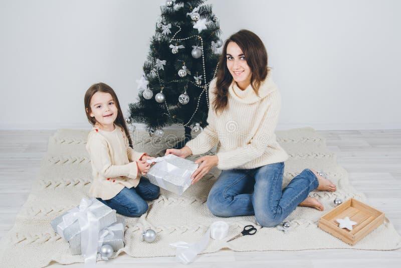 母亲和小女儿包装礼物 免版税图库摄影