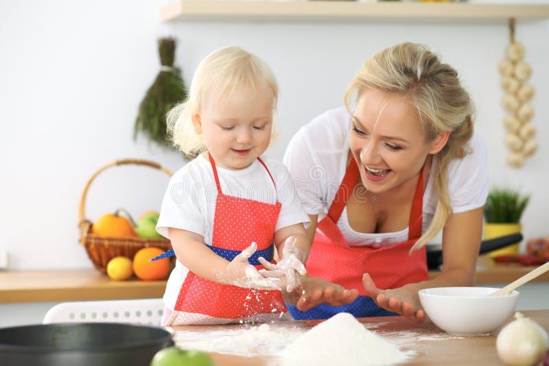 母亲和小女儿在厨房里烹调 一起花费时间全部或愉快的家庭观念 免版税库存图片