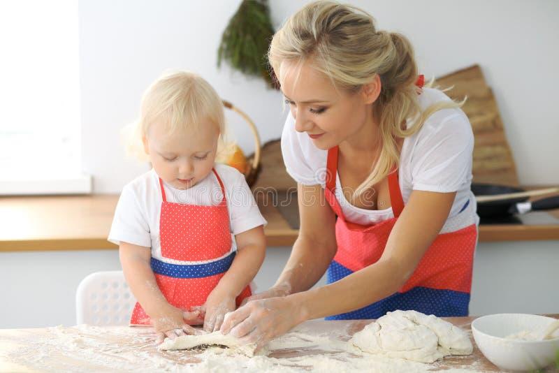 母亲和小女儿在厨房里烹调 一起花费时间全部或愉快的家庭观念 图库摄影