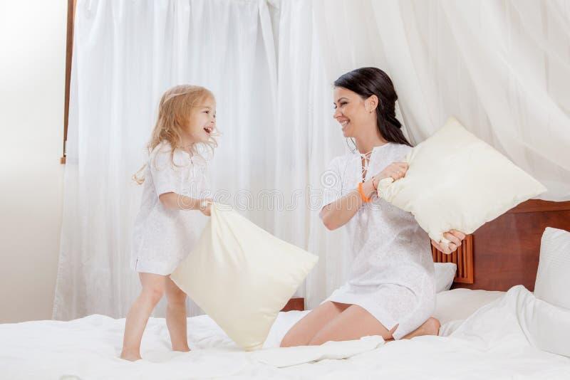 母亲和小女儿在床上 免版税库存照片