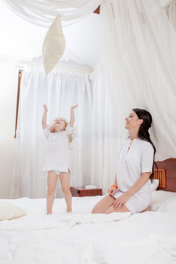 母亲和小女儿在床上 库存图片