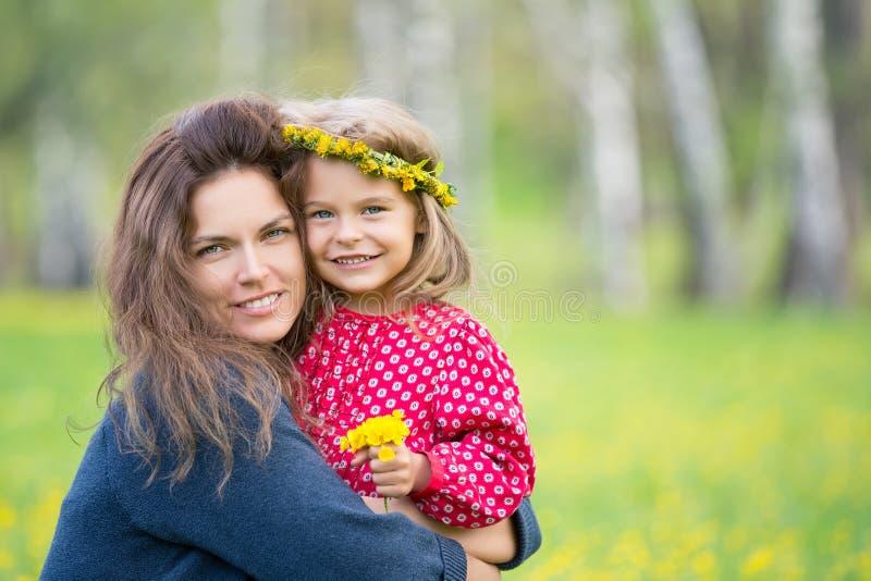 母亲和小女儿在春天公园 库存照片