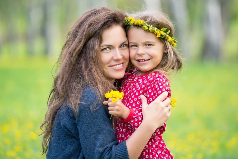 母亲和小女儿在春天公园 免版税库存照片