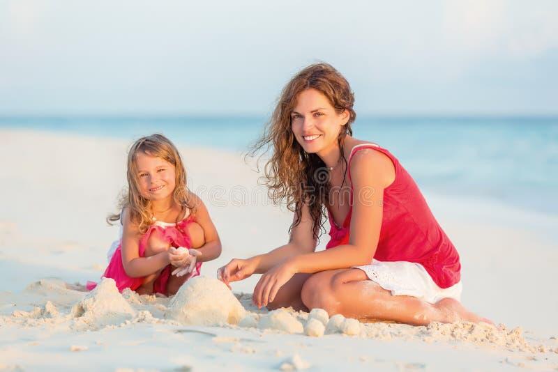 母亲和小女儿在海滩使用 库存照片