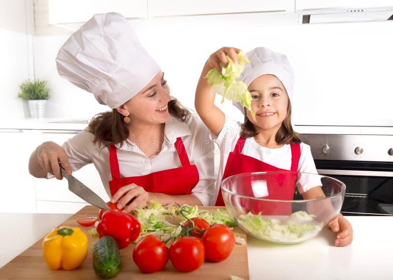 年轻母亲和小女儿房子厨房的沙拉为午餐佩带的围裙和厨师帽子做准备 免版税库存照片