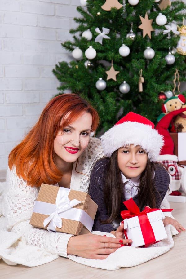 年轻母亲和小女儿有礼物盒和圣诞节的t 库存照片
