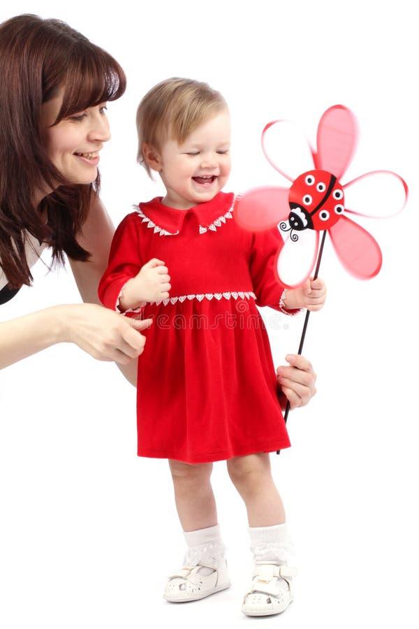 母亲和小女孩使用与玩具的一件红色礼服的 免版税库存图片