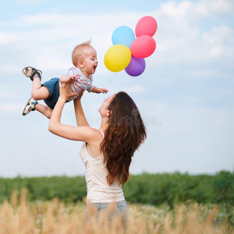 母亲和小孩使用小的儿子户外 图库摄影