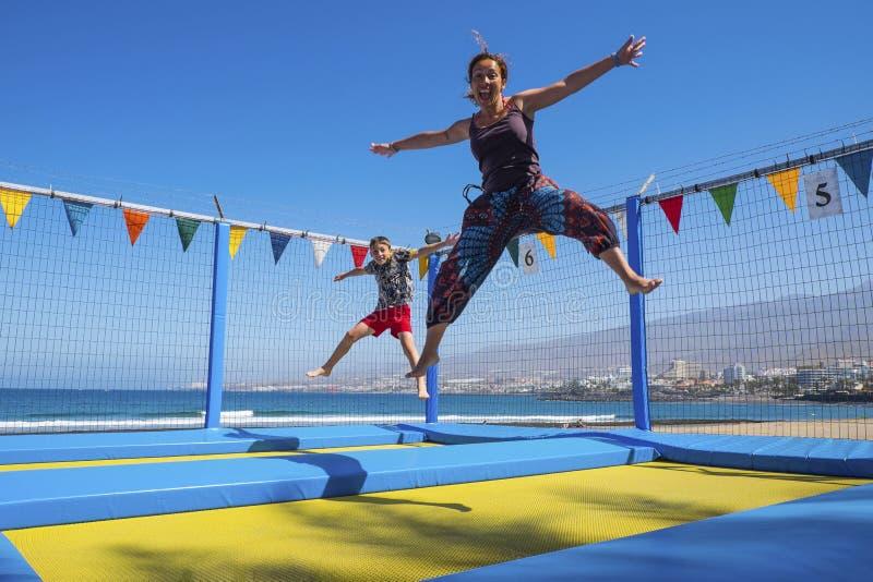 母亲和小孩子使用和跳跃象疯狂的儿子白种人获得很多乐趣在假期 室外娱乐活动为 免版税库存图片