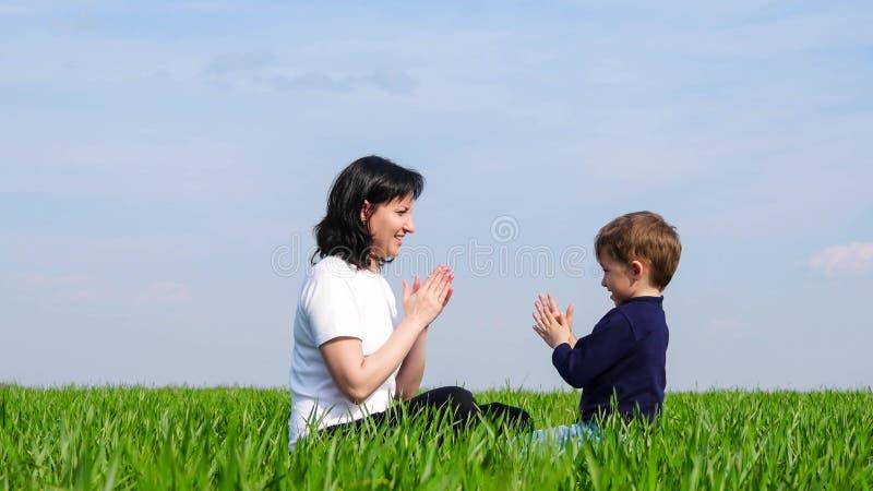 母亲和小孩子坐绿草和戏剧,掴彼此的手 免版税图库摄影