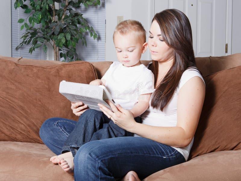 母亲和小孩从无线片剂的儿子读书 免版税库存照片