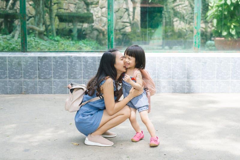 母亲和小的女儿夏天画象在绿色美丽的公园 库存图片